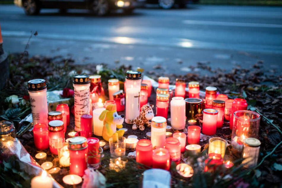 Kerzen und Blumen liegen an der Unfallstelle.