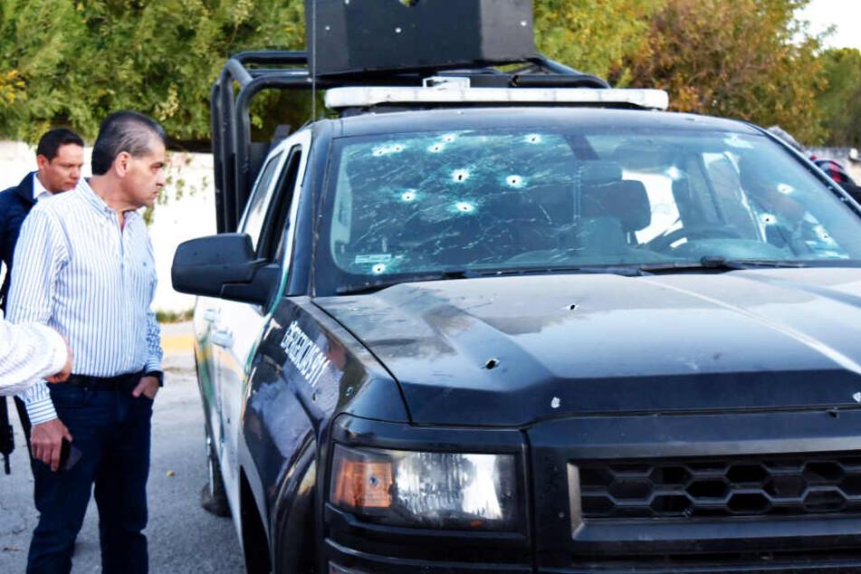 Miguel Riquelme Solis, Gouverneur von Coahuila, betrachtet ein Polizeifahrzeug mit Einschusslöchern.