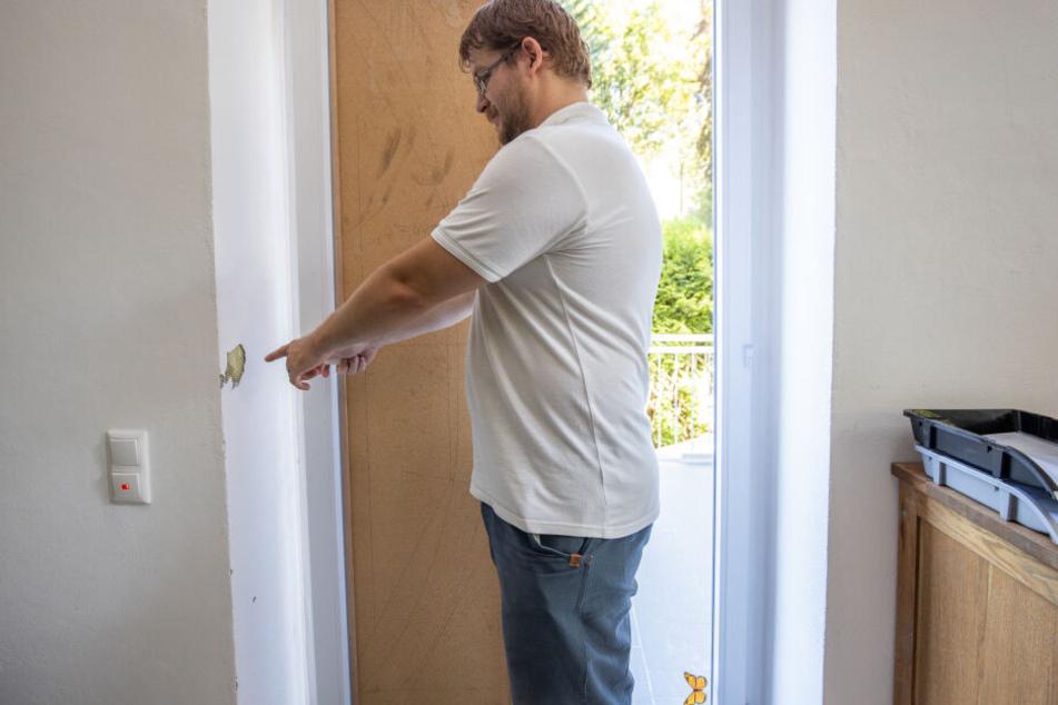 Die zerstörte Tür ist mit einer Spanplatte gesichert: Ein Pflegedienstmitarbeiter (36) zeigt auf die Schäden des Überfalls.