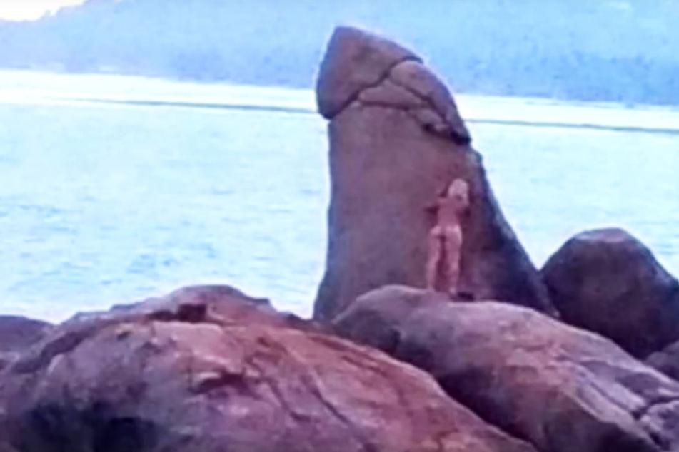 Die nackte Frau hat sichtlich Spaß mit dem Felsen-Penis.