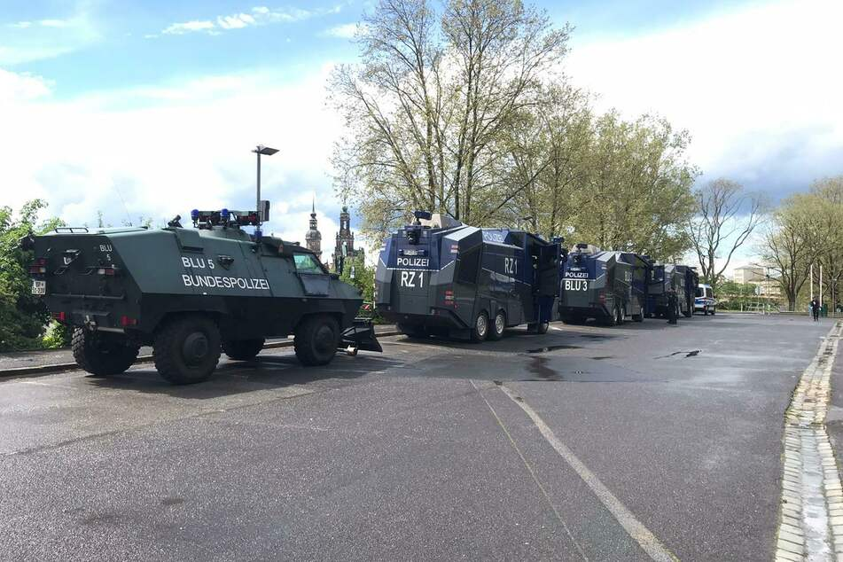 Die Polizei hat sich bereits mit mehreren Fahrzeugen - drei Wasserwerfer und ein Räumpanzer - positioniert.