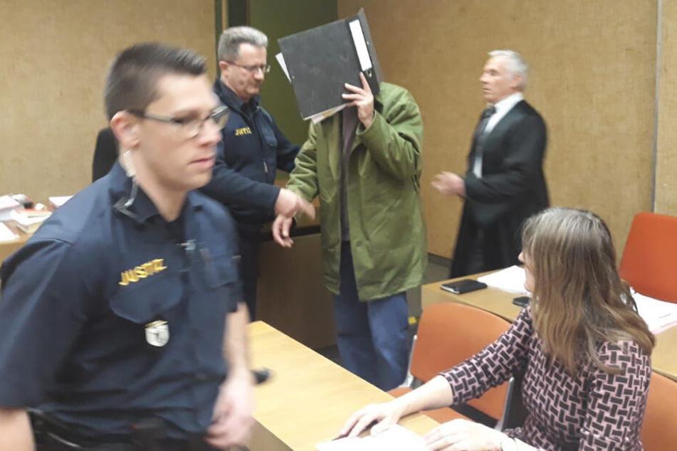 Der Angeklagte (M) wird von Justizbeamten im Amtsgericht in den Verhandlungssaal geführt.