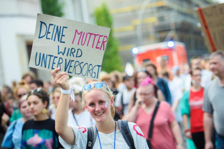 """Eine Teilnehmerin hält auf der Demonstration ein Schild mit der Aufschrift """"Deine Mutter wird unterversorgt""""."""