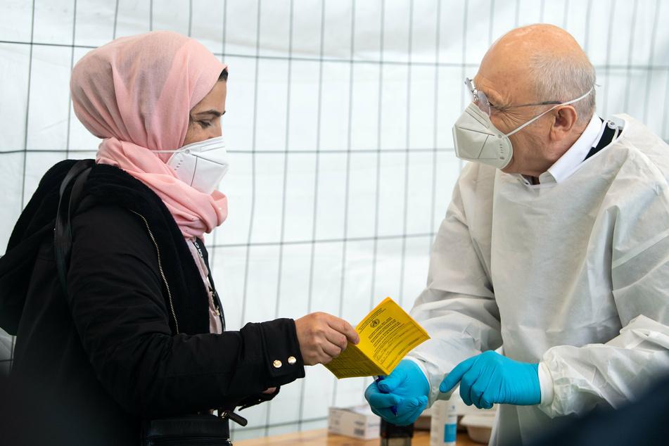 Eine Anwohnerin aus Neukölln lässt sich von Dr. Fatmir Dalladaku in der Turnhalle einer Schule in Neukölln, wo eine Schwerpunktimpfung gegen Corona stattfindet, mit dem Impfstoff von Johnson & Johnson gegen Corona impfen.
