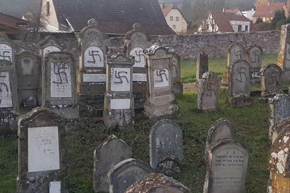 Grabsteine auf einem jüdischen Friedhof wurden mit schwarzen Hakenkreuzen beschmiert.