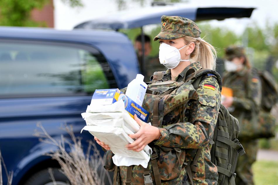Eine Bundeswehrsoldatin trägt Schutzausrüstung in ein Testzelt für ein Corona-Screening. (Symbolbild)