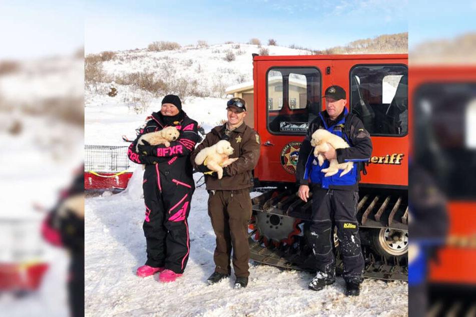 Die Familie und ein Polizist halten die drei Hundewelpen.