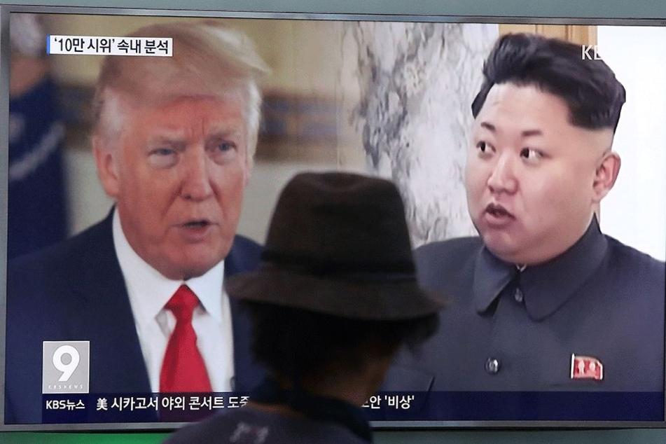 Ein Mann blickt am 10. August in einer Bahnstation in Seoul (Südkorea) auf einen Bildschirm, auf dem von einem Nachrichtensender Bilder von Nordkoreas Staatschef Kim Jong Un (r) und US-Präsident Donald Trump (71) gezeigt werden.