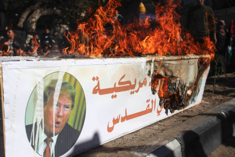 Palästinensische Autonomiegebiete, Gaza: Während eines Protestes am Freitag von Unterstützern der Hamas gegen die USA brennt ein Plakat mit Bildern des US-Präsidenten Trump und des israelischen Premierministers Netanjahu auf einem Holzkasten.