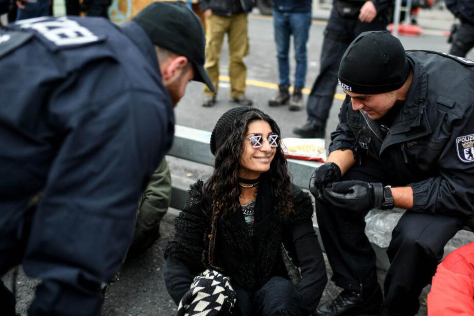 Polizisten versuchen eine Aktivistin auf dem Mühlendamm an der Mühlendammbrücke zum Verlassen der Brücke zu bewegen.
