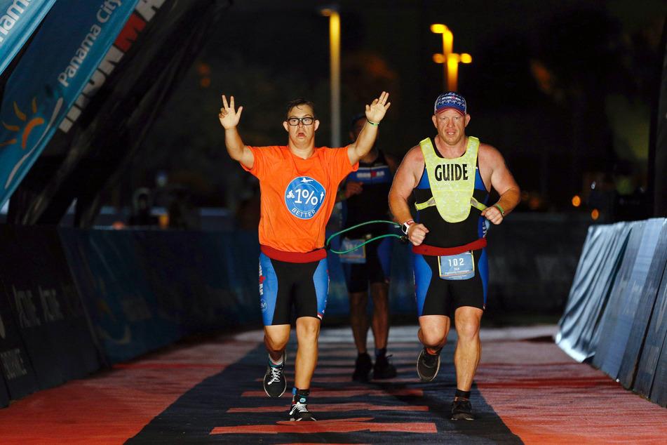 Mit hochgestreckten Armen läuft Chris Nikoc (l) neben seinem Trainer Dan Grieb beim Ironman 2020 über die Ziellinie.