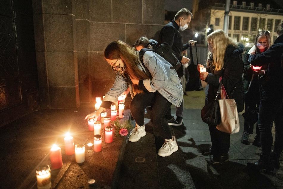 Eine Frau stellt eine Kerze bei einer Gedenkveranstaltung für das Krefelder Todesopfer des Messerangriffs von Dresden auf.