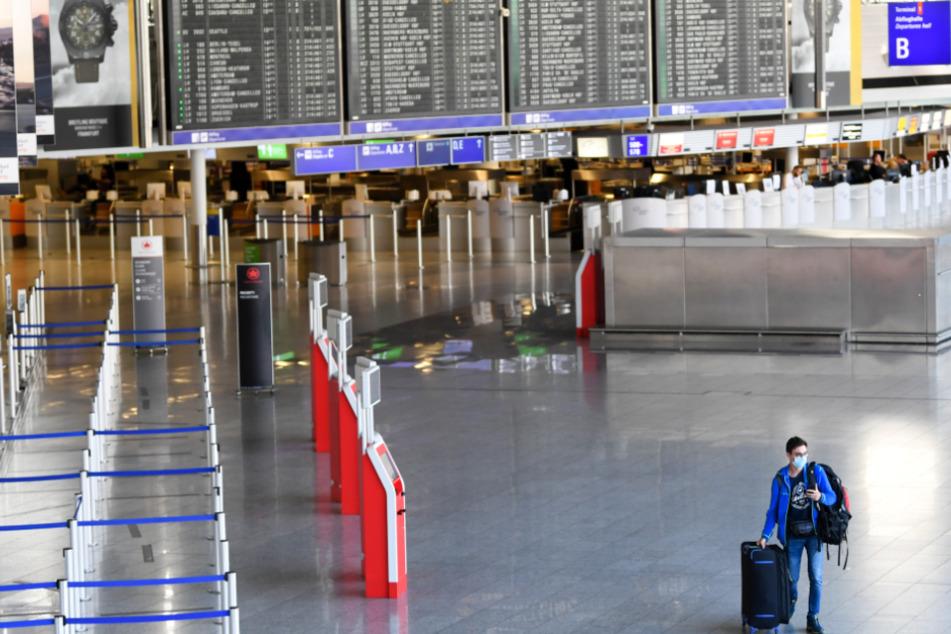 Corona-Krise: Ein Flugreisender geht am Frankfurter Flughafen durch die leere Abflughalle B im Terminal 1.