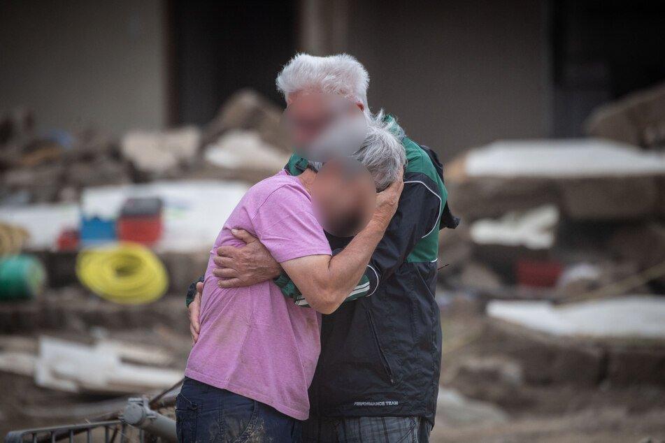 Herzzerreißende Bilder: Weinend liegen sich zwei Brüder vor ihrem von der Flut zerstörten Elternhaus in Altenahr (Rheinland-Pfalz) in den Armen.