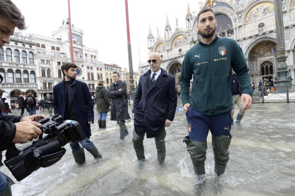 Gianluigi Donnarumma (r.), Fußballtorwart von Italien, kommt während des Hochwassers auf den Markusplatz, um die Betroffenen zu unterstützen.