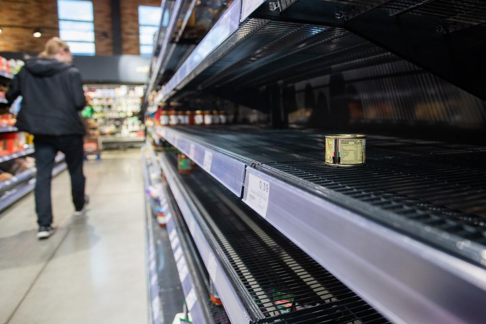 Ein Kunde des Supermarkts läuft an einem leeren Regal vorbei, in dem eine Dose liegt.