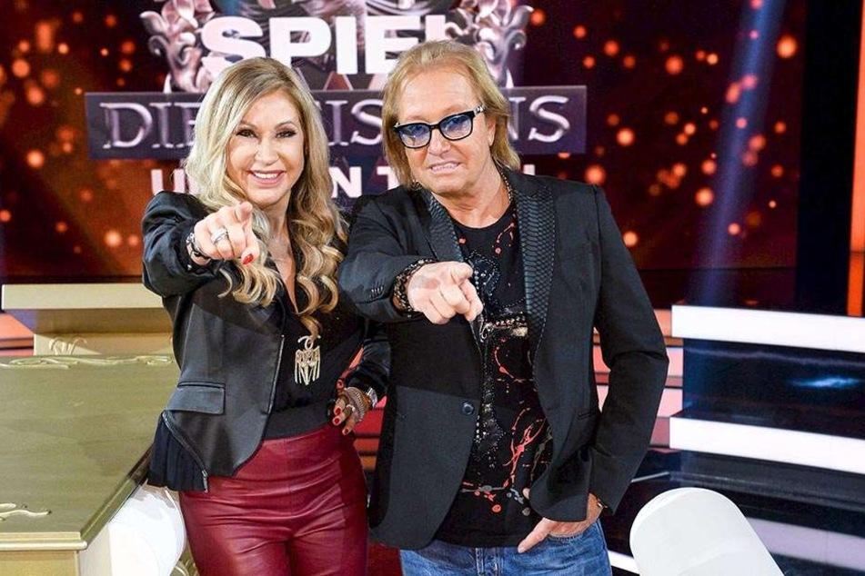 """Die TV-Millionäre Carmen und Robert Geiss stehen in der Kulisse ihrer neuen Show """"Spiel die Geissensuntern Tisch""""."""