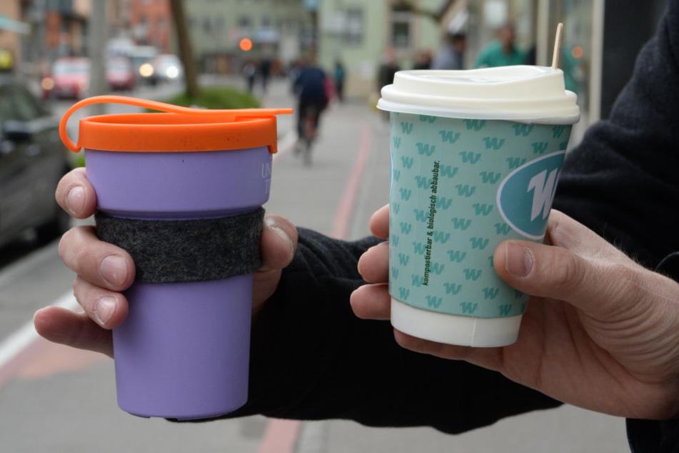 """Ein Mehrweg-Kaffeebecher (l.) und ein Einweg-Kaffeebecher werden gehalten. Das Aktionsbündnis """"Müllarmes Tübingen"""" stellte im Rahmen einer Pressekonferenz den Mehrwegbecher """"treecup""""."""