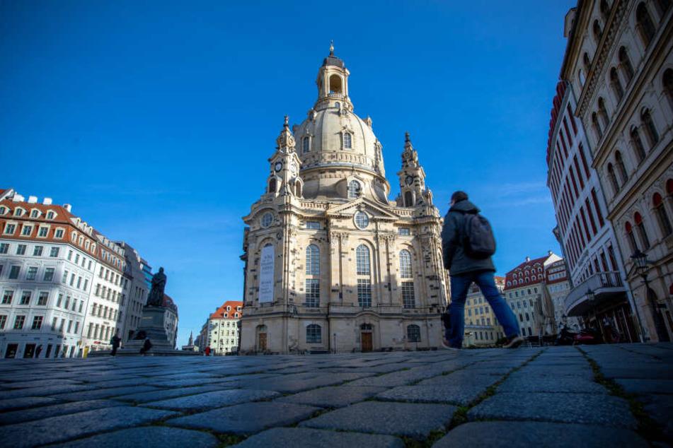 Passanten gehen am Morgen an der Frauenkirche vorbei.
