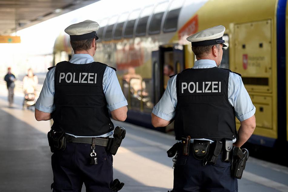 Zwei Polizisten vor einer Regionalbahn. (Symbolbild)