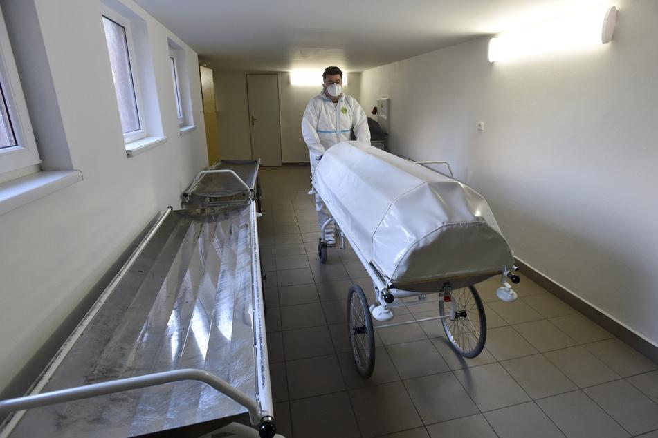 Tschechien, Zlin: Ein medizinischer Mitarbeiter in Schutzkleidung schiebt eine Leiche in die Pathologie des Regionalkrankenhauses.
