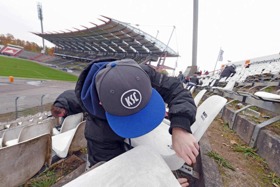 Fans des Fußball-Drittligisten Karlsruher SC demontierten im Wildparkstadion Karlsruhe Sitzschalen, bevor im Oktober 2018 die Abrissarbeiten im Stadion begannen.