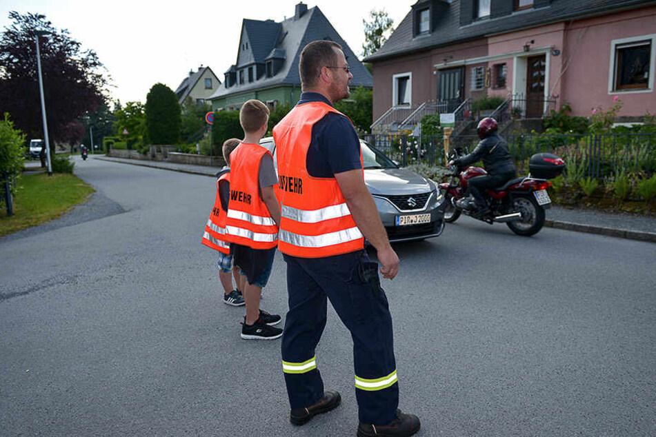 Freiwillige Feuerwehr Berggießhübel im Einsatz: Robert Smyrtek (37, v.r.), Jason (13) und Lenny (9) sperren die Ortsdurchfahrt ab.