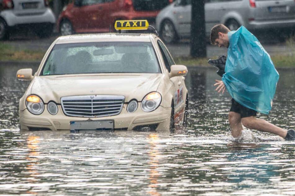 Ein Fußgänger und ein Taxi kämpfen sich durch die Regenmassen.