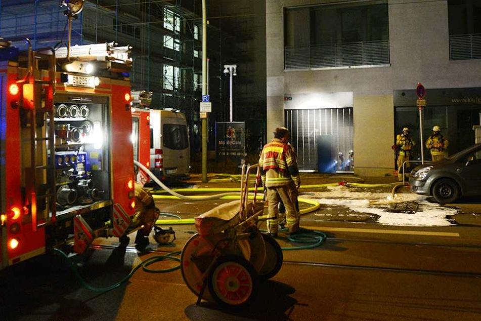 Feuerwehrmänner stehen in Berlin vor der Einfahrt einer Tiefgarage, in der mehrere Autos in Brand geraten waren.