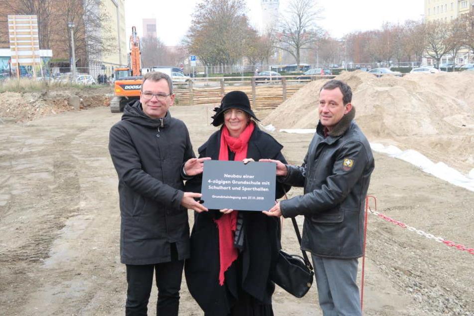 Baubürgermeisterin Dorothee Dubrau (Mitte) zusammen mit Architekt Benedikt Schulz (links) und Nicolas Tsapos, Amtsleiter für Jugend, Familie und Bildung (rechts), bei der Übergabe der Erinnerungstafel.