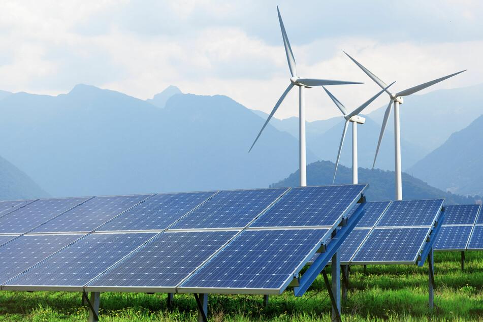 Energiewende: Sonnenkollektoren und Windräder vor Bergkulisse (123rf.com/Iaroslav Danylchenko).