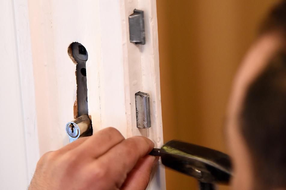 Ein Mitarbeiter eines Schlüsseldienstes baut ein defektes Türschloss aus. (Symbolbild)