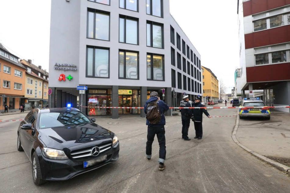 Polizisten stehen vor einem abgesperrten Gebäude. Zuvor wurde ein verdächtiges Paket gemeldet.