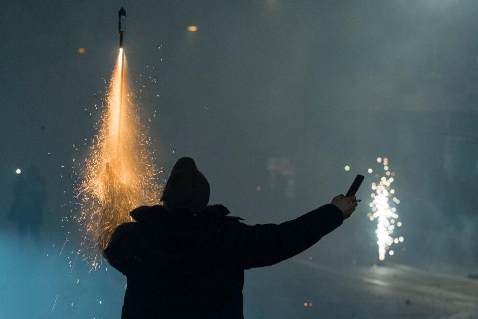 Während er mit der linken Hand eine brennende Rakete hält, filmt sich ein Mann bei der Aktion selbst mit seinem Smartphone.