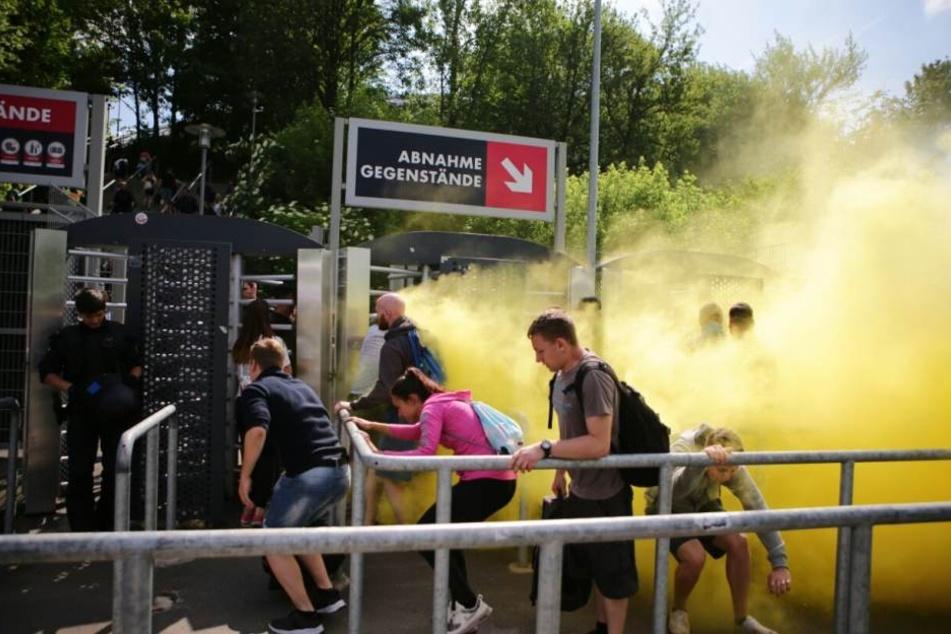 Rauchbomben wurden gezündet, Fans hasteten unter den Absperrungen hindurch.