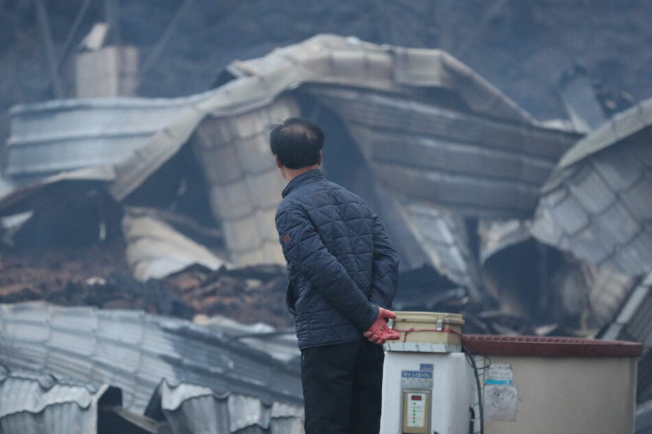 Ein Mann betrachtet in Südkorea ein völlig ausgebranntes Haus.