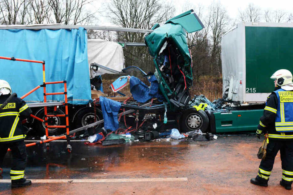 Rettungskräfte stehen vor dem verunglückten Lastwagen.