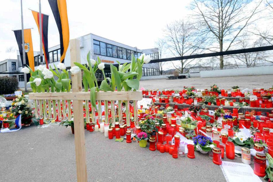 Ein Holzkreuz mit 16 weißen Tulpen steht am 20.03.2009 vor der Albertville-Realschule in Winnenden.