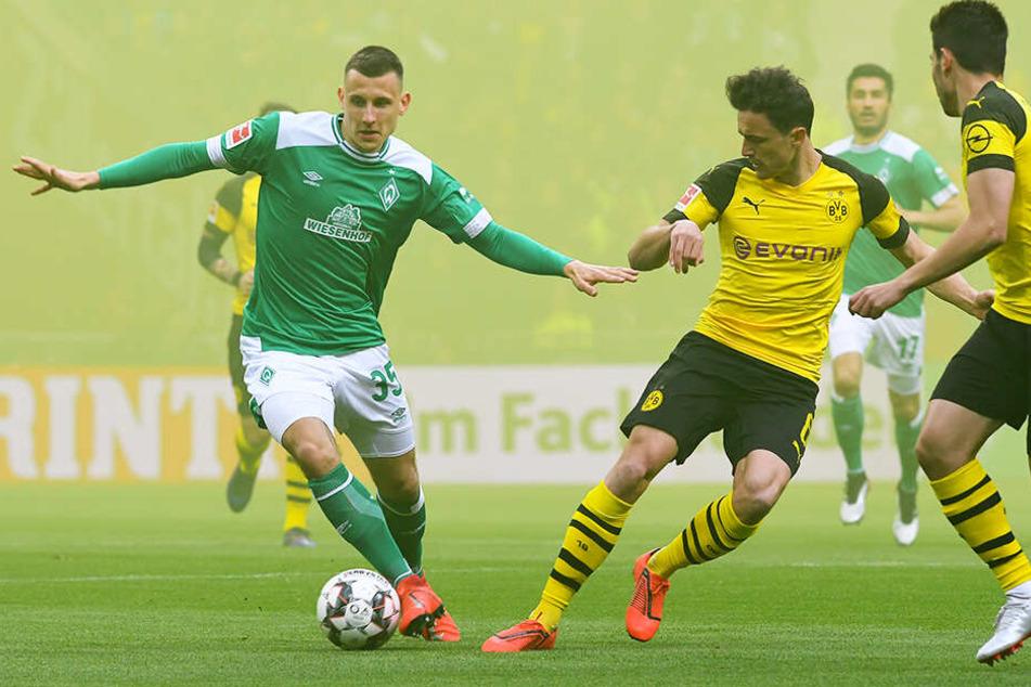 Bremens Maximilian Eggestein (l.) duelliert sich im dichten Nebel mit Dortmunds Thomas Delaney (M.).