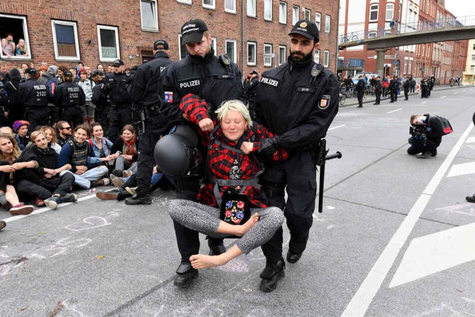 Polizisten räumen nach einer Protestaktion gegen Autoverkehr auf der vielbefahrenen B75, dem Theodor Heuss Ring, eine mehrstündige Sitzblockade.