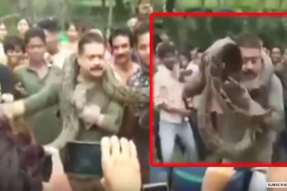 Zunächst posiert der Mann noch mit der Schlange für Fotos, dann hat sie ihn fest in ihrem Würgegriff. Nur mit Not kann er sich befreien.
