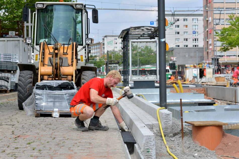 Die Haltestellen-Häuschen stehen schon: Patrick Wolf (27) schlägt die Entwässerungsrinnen für die Bahnsteige ein.