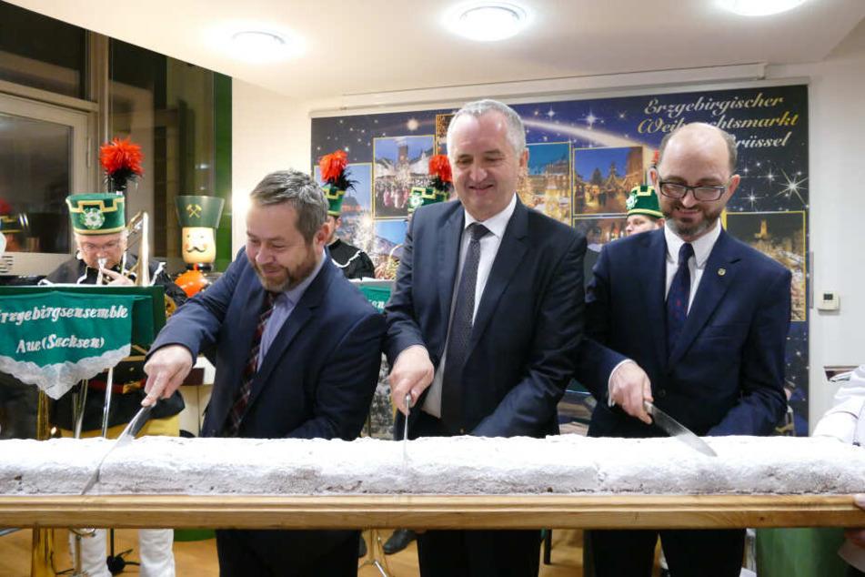 Staatsminister Thomas Schmidt (58, Mitte) schneidet den Stollen beim Erzgebirgischen Weihnachtsmarkt in Brüssel an.