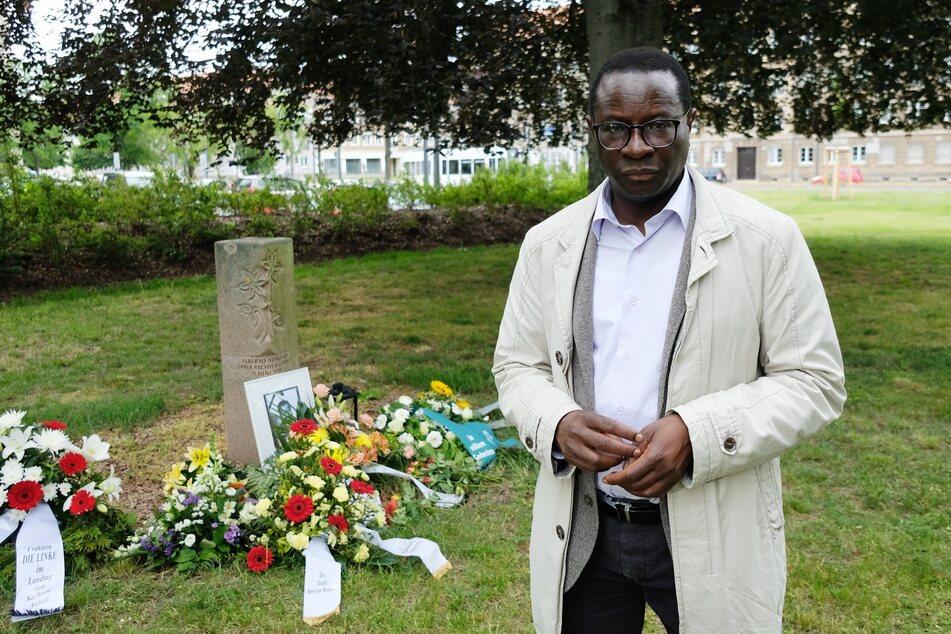 Karamba Diaby (58), SPD-Bundestagsabgeordneter, steht am Gedenkstein im Stadtpark von Dessau.