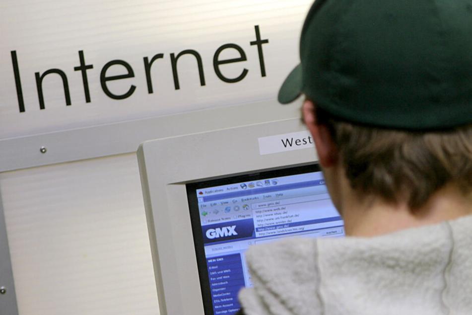 Ein Mann schreibt auf einem Computer eine E-Mail (Symbolbild).
