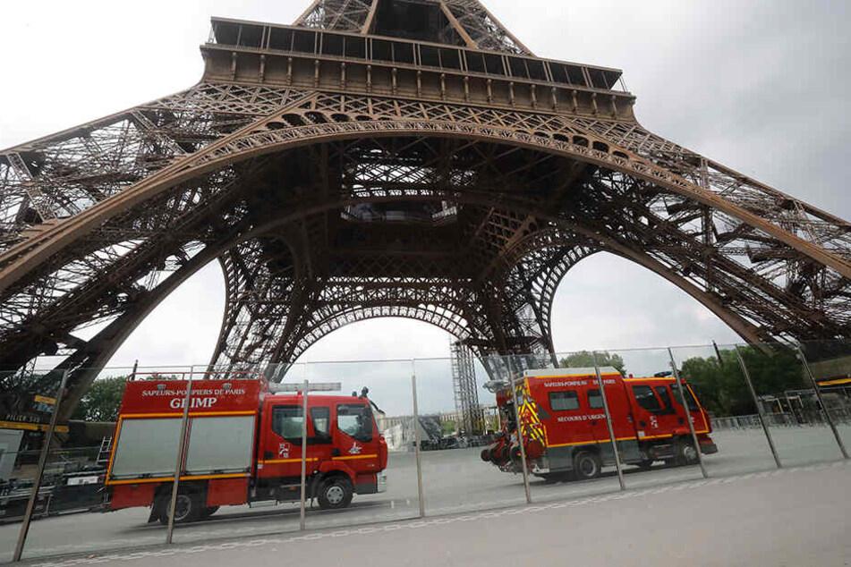 Rettungsdienstfahrzeuge stehen am Eiffelturm. Das Pariser Wahrzeichen wurde am Montag wegen eines Kletterers für Besucher gesperrt.