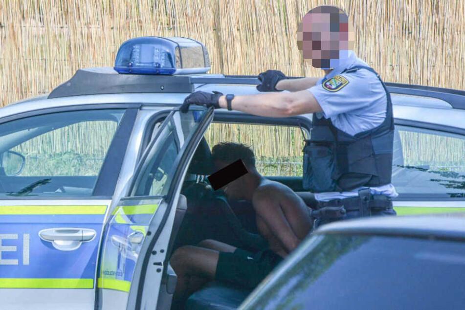 Einer der Täter sitzt nach dem Angriff in Handschellen in einem Polizeiauto und wird von einem Beamten bewacht.