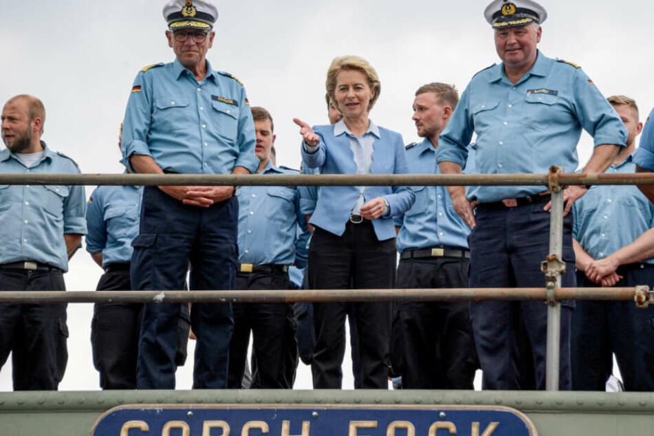 Ursula von der Leyen steht gemeinsam mit der Besatzung an Bord.
