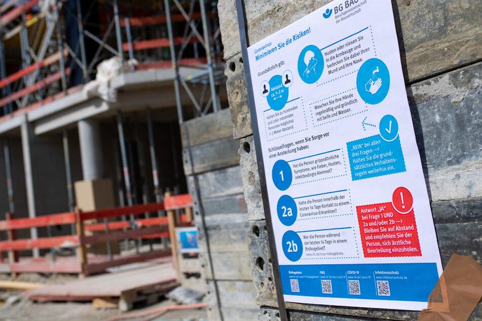 Ein Schild mit Informationen über das Coronavirus ist auf der Baustelle des neuen Strafjustizzentrums zu sehen.