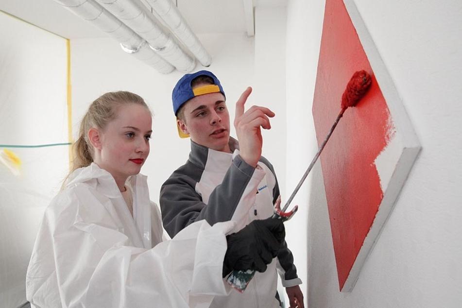 Maler-Azubi Maximilian Born (20) zeigt Johanna Lehmann (13) wie man den  Pinsel schwingt